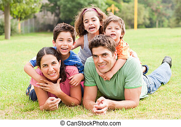 Happy family lying in the park