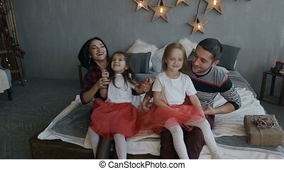Happy family lying on bed at home in the evening. Christmas evening
