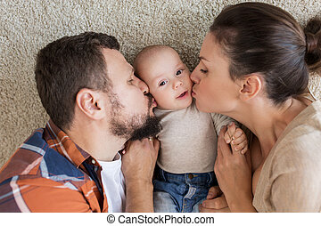 happy family lying on floor and kissing their baby
