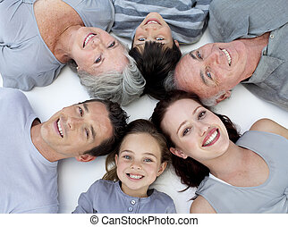 Happy family lying on floor with heads together