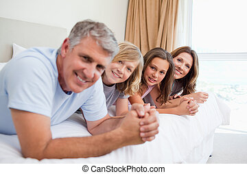 Happy family lying on the bed