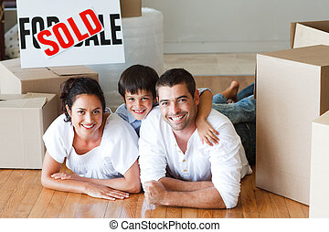 Happy family lying on the floor after buying house with...