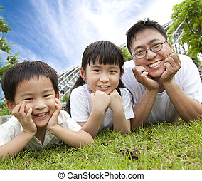 happy family lying on the grass. father with son and daughter