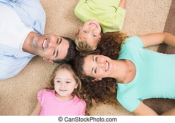 Happy family lying on the rug in a circle