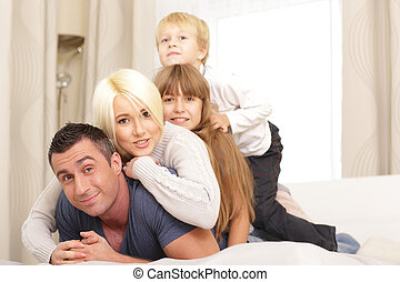 Happy family lying on top of each other on white bed in the bedroom