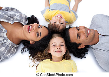 Happy family lying together on the floor in circle against a white background