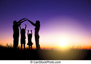 happy family making home sign on the hill with sunrise background