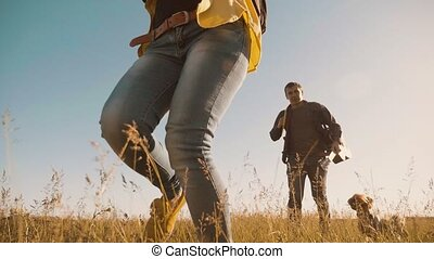happy family Man and woman are running slow motion video walking on nature girl run in a field on trekking trip. tourists with a guitar backpacks traveling. happy lifestyle family couple run travel tourism concept