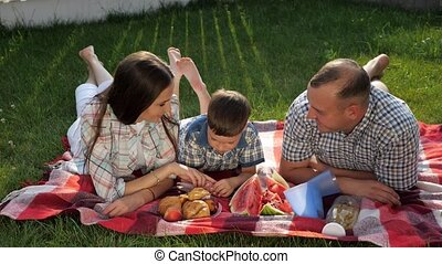 happy family members lie on stomach on red blanket at picnic...