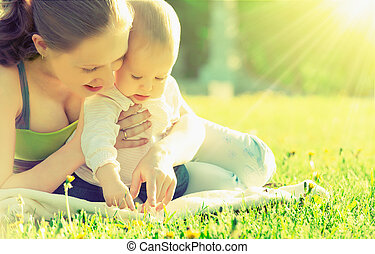 happy family. Mom and baby resting in a meadow in the summer outdoors in the park