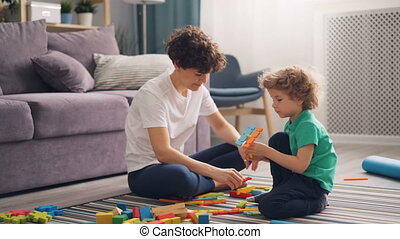 Happy family mom and child playing with toys at home sitting on floor together