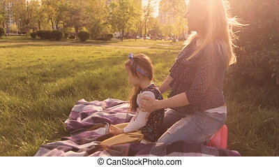 Happy family, mom and daughter playing in the meadow