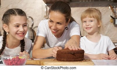Happy family mom and daughters are cooking birthday cake together.