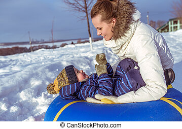 Happy family mom and son playing on tubing in cold weather. In the winter in the city on a toy, fresh frosty air in December and January.