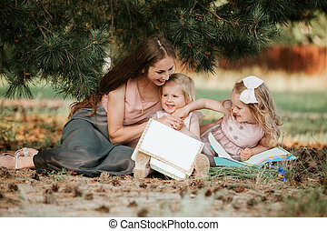 Happy family - mom and two daughters are sitting in a meadow and reading a book. Picnic. happy family, mom and two daughters. Mother's day concept