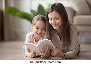 Happy family mom baby sitter and kid daughter reading book
