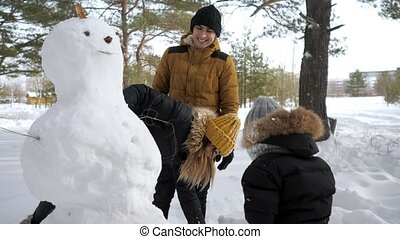 Happy family mom, dad and son are making a snowman in winter city park.