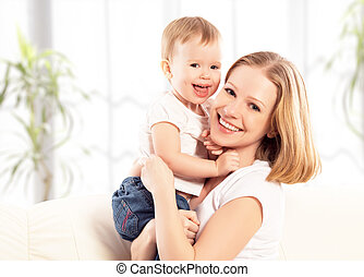 happy family. Mother and baby daughter at home on the sofa