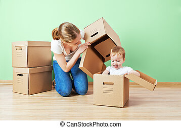 happy family mother and baby daughter in an empty apartment near the wall with cardboard boxes relocation