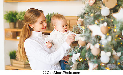 family mother and baby decorate Christmas tree