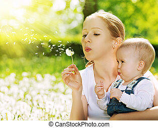 happy family. Mother and baby girl blowing on a dandelion ...