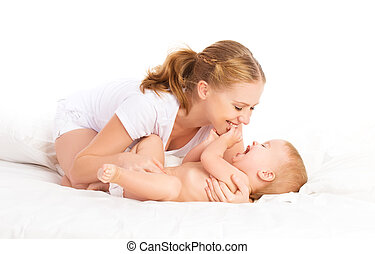 happy family mother and baby having fun playing, laughing on bed