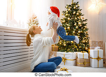 family mother and baby son at Christmas morning at tree -...
