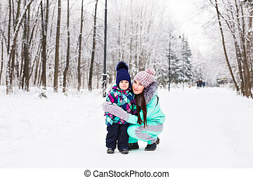 happy family mother and child baby daughter on a winter walk in the woods
