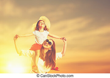 happy family mother and child daughter on beach at sunset