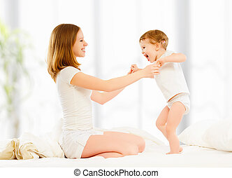 happy family mother and child daughter playing and laughing baby kissing in bed