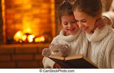 happy family mother and child daughter read a book on  winter evening