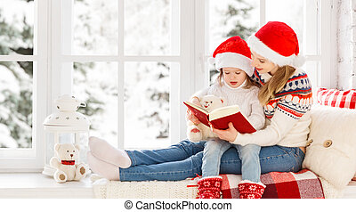 happy family mother and child daughter reading book on winter window