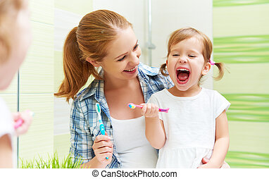 happy family mother and child girl cleans teeth with toothbrush in bathroom