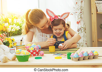 happy family mother and child girl paints eggs for Easter