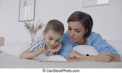 Happy family mother and child son with tablet in evening. Happy family mother and child son with tablet in evening before bed