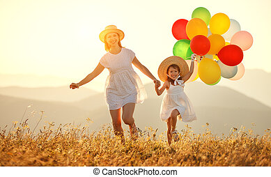 happy family mother and child with balloons at sunset in summer
