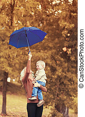 Happy family mother and child with umbrella in autumn day
