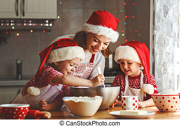happy family mother and children bake cookies for Christmas...