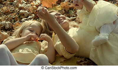 Happy family mother and children in autumn park