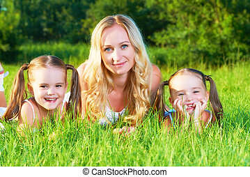 happy family mother and children twin sisters on meadow in summer on grass