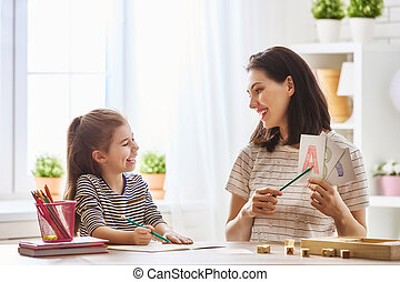 woman teaches child the alphabet - Happy family. Mother and ...
