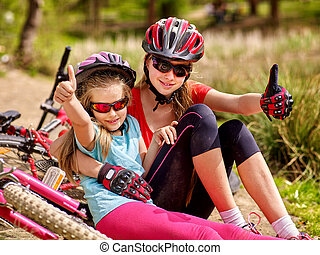 Happy family. Mother and daughter are on road near bicycles.