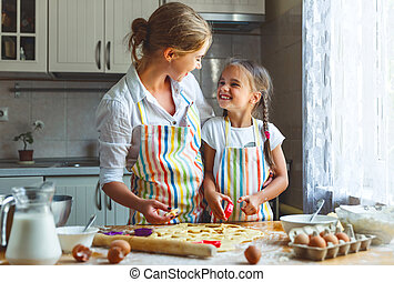 Happy family mother and daughter bake kneading dough in...