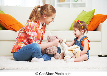 happy family mother and daughter child girl playing with toy teddy bear