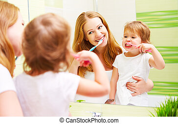 happy family mother and daughter child brushing her teeth...