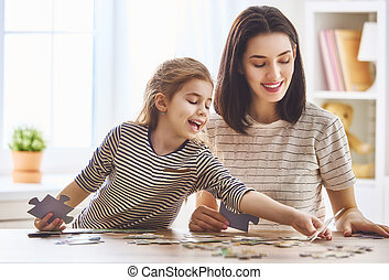 Mother and daughter do puzzles - Happy family. Mother and...