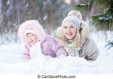 Happy family mother and daughter  playing with snow in winter outdoor