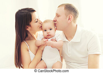 Happy family, mother and father kissing baby in white room