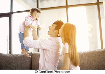 happy family mother and father playing with baby at home