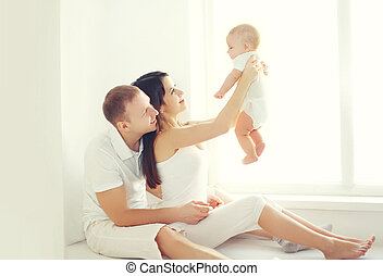 Happy family, mother and father playing with baby home in white room near window